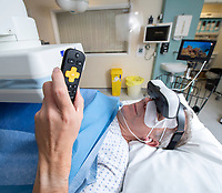 BNPS.co.uk (01202 558833)<br /> Pic: PhilYeomans/BNPS<br /> <br /> Carry On Doctor...patients can channel surf whilst under the knife.<br /> <br /> Dr Clare Bent at the Royal Bournemouth Hospital is pioneering the unique procedure.<br /> <br /> An NHS hospital has become the first in Britain to give anxious patients video goggles to distract them during operations.<br /> <br /> Patients can watch a whole movie or TV box sets through the hi-tech headsets while they have surgery under local anaesthetic.<br /> <br /> Horror films or laugh-out-loud comedies are not advised as they could make the casualty jolt and squirm around too much as they go under the knife.<br /> <br /> The Royal Bournemouth Hospital is now trialling the Wi-Fi enabled goggles in the hope they will actually save money.<br /> <br /> With the patient being more at ease they will not have to be sedated and will recover and leave hospital quicker, freeing up valuable bed space.