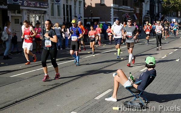 Nederland - Amsterdam - 2017 . De Marathon van Amsterdam. Vrouw met biertje bekijkt de deelnemers.    Foto Berlinda van Dam / Hollandse Hoogte