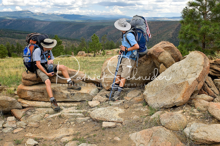 Photo story of Philmont Scout Ranch in Cimarron, New Mexico, taken during a Boy Scout Troop backpack trip in the summer of 2013. Photo is part of a comprehensive picture package which shows in-depth photography of a BSA Ventures crew on a trek.  In this photo BSA Venture Crew Scouts take a break from hiking to take in mountain range views in the backcountry at Philmont Scout Ranch.   <br /> <br /> The  Photo by travel photograph: PatrickschneiderPhoto.com