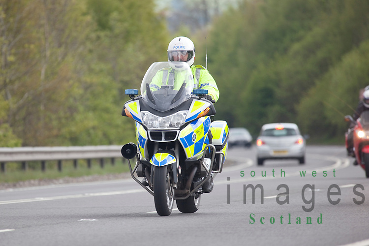 Police motorcycle motorcyclist riding motorbike on dual carriage way near Dumfries UK