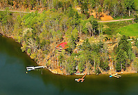 Aerial photography of and around Watauga Lake, Tenn., taken April 2011. Surrounded by the Cherokee National Forest, the vast majority of Watauga Lake's shoreline and surrounding mountains is undeveloped and pristine. Even during busy holiday weekends (photo taken on Easter weekend 2011) the large lake is rarely busy with boaters. Photo shows Whipkins Cove, vacation rental property (red roof log home on left).