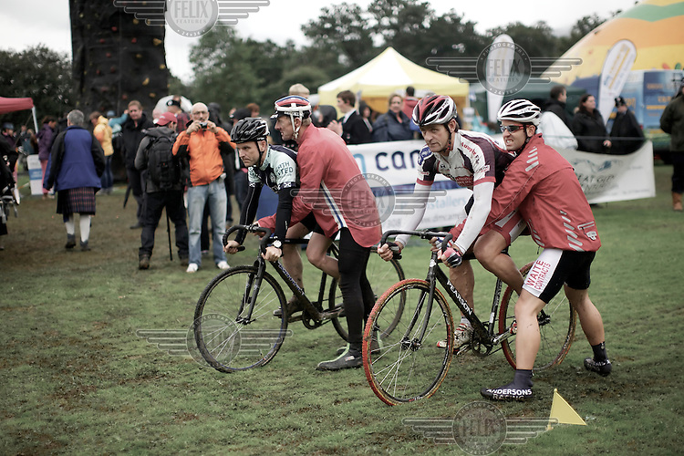 Men get a push start on the wet grass as they compete in the cycling event at the Pitlochry Highland Games in Perthshire.