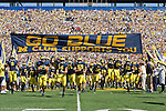 "30 August 2008: Michigan players run under the ""Go Blue"" banner before an NCAA college football game between the Michigan Wolverines and the Utah Utes, at Michigan Stadium in Ann Arbor, Michigan. Utah upset Michigan, winning 25-23."
