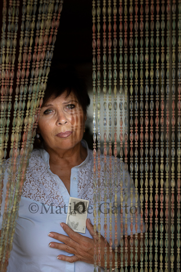 "Spain - Terrassa - Portrait of Isabel Maria Gil Pérez, 62. Isabel Maria Gil Pérez sits in her living room in the city centre of Terrassa, its shutters half-closed to protect it from the scorching midday sun. In dim light, her melancholic hazelnut eyes look at a small, faded photo showing a 20-year-old woman and her newborn baby. ""This is the only souvenir I have of my son Raul"", she explains, carefully holding the picture between her fingers. ""Without it, what happened would have only been a nightmare""."
