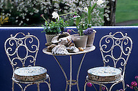 Large sea shells and potted plants on a weathered table are flanked by a pair of white wrought iron chairs on an urban terrace