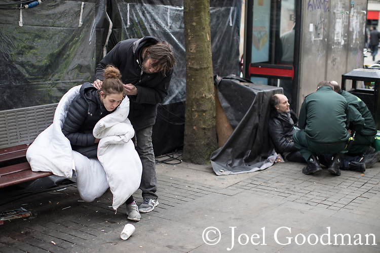 © Joel Goodman - 07973 332324 . 06/04/2017 . Manchester , UK . A man carefully cleans off the face of a woman , who appears disorientated as she sits on a bench wrapped in a duvet , as behind paramedics tend to a man lying on the ground . An epidemic of abuse of the drug spice by some of Manchester's homeless population , in plain sight , is causing users to experience psychosis and a zombie-like state and is daily being witnessed in the Piccadilly Gardens area of Manchester , drawing large resource from paramedic services in the city centre . Photo credit : Joel Goodman
