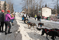 Charley Bejna and team run past spectators on the bike/ski trail with an Iditarider in the basket during the Anchorage, Alaska ceremonial start on Saturday, March 5, 2016 Iditarod Race. Photo by O'Hara Shipe/SchultzPhoto.com