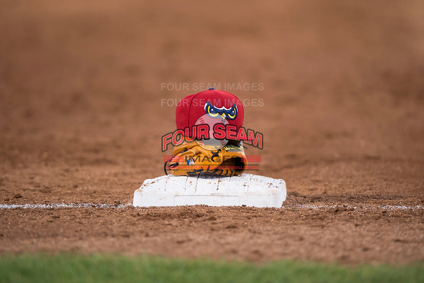 An Orem Owlz hat rests on a glove at third base during a Pioneer League game against the Ogden Raptors at Home of the OWLZ on August 24, 2018 in Orem, Utah. The Ogden Raptors defeated the Orem Owlz by a score of 13-5. (Zachary Lucy/Four Seam Images)