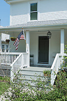 The exterior of a New England clapboard house with grey painted steps leading up to a veranda.