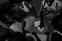 Girls playing cards at the Doctors Without Borders (MSF; Medecins Sans Frontieres) tent compound. This compound is one of the few places children, known as Night Commuters, can find protection every  night to avoid being abducted by the Lords Resistance Army (LRA) in Northern Uganda. The LRA is primarily made up of abducted youth. Night Commuters find much more than safety in the compounds, they also find friendships, activity and fellowship. Tens of thousands of children, on average, make this exodus every evening. The war in Northern Uganda has been transpiring for two decades. Lachor, Gulu District, Uganda, Africa. December 2005 © Stephen Blake Farrington
