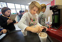 STAFF PHOTO JASON IVESTER --12/18/2014--<br /> Tabatha (cq) Snyder (left) checks orders as Hannah Bendsten (cq) stirs hot chocolate to be delivered to classrooms on Thursday, Dec. 18, 2014, inside Sugar Creek Elementary School in Bentonville. Third-graders at the school sold hot chocolate and snacks to students and staff to raise money for the Northwest Arkansas Children's Shelter.
