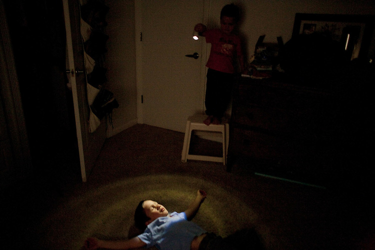 On a cold rainy afternoon, my sons amuse themselves in my bedroom with my flashlight.