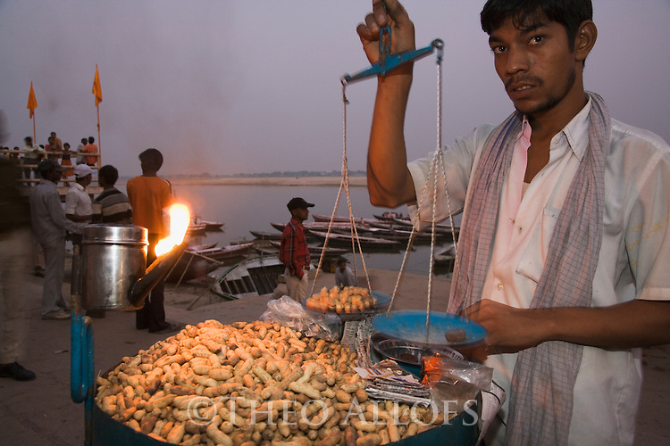 Indian man selling roasted peanuts on Ghats (stairs) at Ganges River at dusk;  Varanasi has been a cultural and religious center in northern India for several thousand years, Varanasi, Uttar Pradesh, India --- Model Released