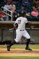 Birmingham Barons left fielder Eloy Jimenez (21) follows through on a swing during a game against the Pensacola Blue Wahoos on May 8, 2018 at Regions FIeld in Birmingham, Alabama.  Birmingham defeated Pensacola 5-2.  (Mike Janes/Four Seam Images)