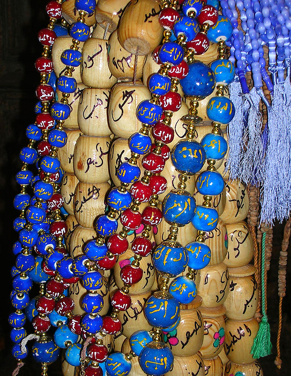Glass beads in red, blue and light blue and beads made of light wooden all inscribed with Egyptian symbols hanging in the marketplace in Cairo.