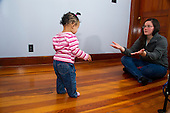 MR / Schenectady, NY. Infant in early walking stage (girl, 12 months, African American & Caucasian) exhibits 12-month-old human development milestone behavior as she walks towards her mother (21) as she holds her arms out to encourage her daughter. MR: Dal4, Dal6. ID: AL-HD. © Ellen B. Senisi