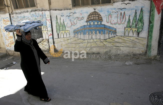 "A Palestinian woman walks in a street in the West Bank Balata refugee camp, near Nablus on May 11, 2011, as Palestinians mark the 63rd anniversary of the ""Nakba"" (catastrophe). Nakba means ""catastrophe"" in reference to the birth of the state of Israel 63 years ago in British-mandate Palestine, which led to the displacement of hundreds of thousands of Palestinians who either fled or were driven out of their homes during the 1948 war over Israel's creation. Photo by Wagdi Eshtayah"