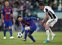 Football Soccer: UEFA Champions UEFA Champions League quarter final first leg Juventus-Barcellona, Juventus stadium, Turin, Italy, April 11, 2017. <br /> Barcellona's Lionel Messi (l) in action with Juventus Mario Mandzukic (r) during the Uefa Champions League football match between Juventus and Barcelona at the Juventus stadium, on April 11 ,2017.<br /> UPDATE IMAGES PRESS/Isabella Bonotto