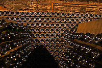 In the wine cellar: Bottles in racks (pupitres) for remuage (riddling of the bottles) to make the sediment move down to the cork. At the back bottles laying sur lattes, the Union Champagne cooperative, also called Champagne de Saint Gall in Avize, Cote des Blancs, Champagne, Marne, Ardennes, France