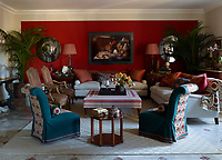 The living room is a rich combination of cream, that blends with the stone floors, and a warm earthy shade of terracotta. Napoleon III slipper chairs are covered in a vintage wool felt with panels of an embroidered suzani by Robert Kime, the ottoman is slipcovered in a custom-stripe linen by Twill Textiles, and the custom-made sofas are upholstered in a linen by Belgian Huis; the Louis XV fauteuils were purchased at Sotheby's, convex antiqued mirrors by Alessandra Branca flank a photograph by Kevin Best, and a custom rug tops the original 1930s marble flooring.