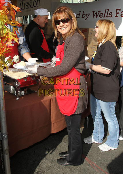 LINDA GRAY .Los Angeles Mission And Anne Douglas Center's Thanksgiving Meal For The Homeless held at The Los Angeles Mission, Los Angeles, CA, USA, .24th November 2010..full length food sunglasses red apron .CAP/ADM/KB.©Kevan Brooks/AdMedia/Capital Pictures.