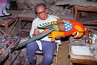 Man painting papier mache bird at Sermel papier mache factory in Tonala. Guadalajara, Mexico.