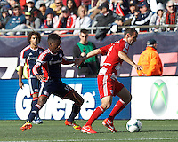 FC Dallas midfielder Andrew Jacobson (4) dribbles at midfield as New England Revolution midfielder Clyde Simms (19) defends..  In a Major League Soccer (MLS) match, FC Dallas (red) defeated the New England Revolution (blue), 1-0, at Gillette Stadium on March 30, 2013.