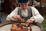 A girl plays with a wooden village puzzle at the Renaissance Pleasure Faire at Santa Fe Dam Recreation Area, Los Angeles, County, CA