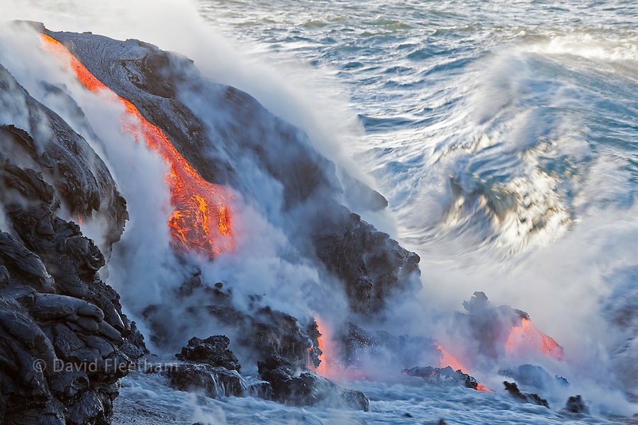 Sea water and molten rock splatter together as a wave crashes onto the Pahoehoe lava flowing from Kilauea into the Pacific Ocean near Kalapana, Big Island, Hawaii.