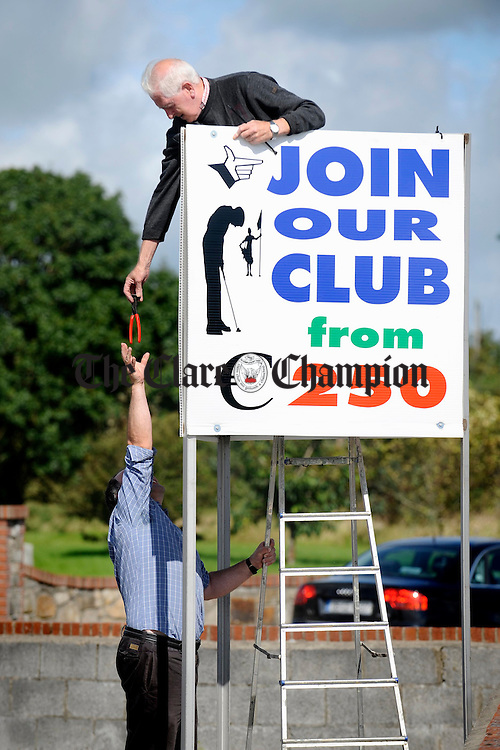 Sean Lyons and Jim Clune fixing some advertising hoardings at Kilrush Golf Club recently. Photograph by John Kelly.