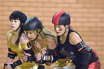 Swansea City Slayers flat track roller derby team (black) take on the Bridgend Bombshells (gold) during their bout at Neath Sports Centre this weekend..