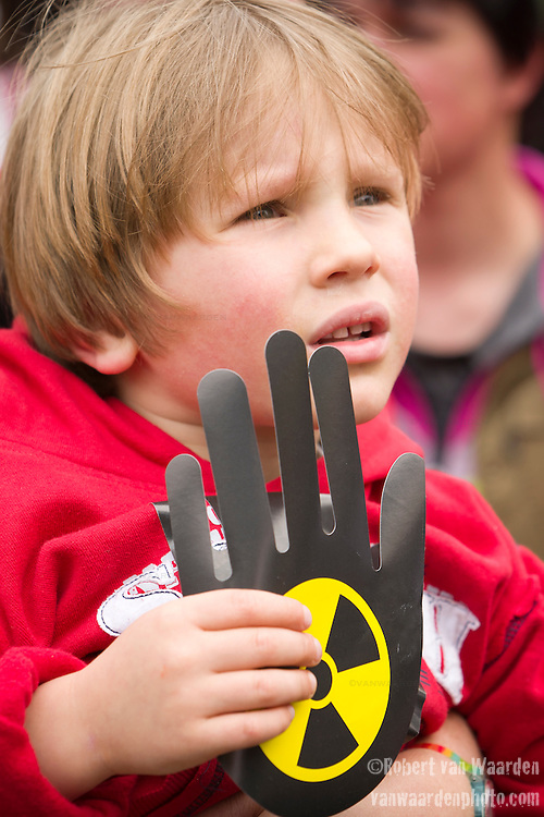 A young boy listens to presenters while holding and anti nuclear sign at an Anti Nuclear Rally held on the Dam Square in Amterdam, the Netherlands on April 16, 2011. Thousands of people gathered on the square to protest recent Netherlands government movements to increase nuclear power in the country.