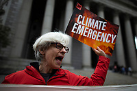 NEW YORK, USA - October 22: A woman shouts slogans agains Exxon as she takes part in a protest against ExxonMobil before the start of its trial outside the New York State Supreme Court building on October 22, 2019 in New York, USA. the trial will establish whether Exxon Mobil, the country's largest fossil fuel company, lied to investors about the cost of carbon emissions to its business. (Photo by Eduardo MunozAlvarez/VIEWpress)