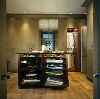A glass-fronted chest of drawers occupies the centre of this impressive dressing room