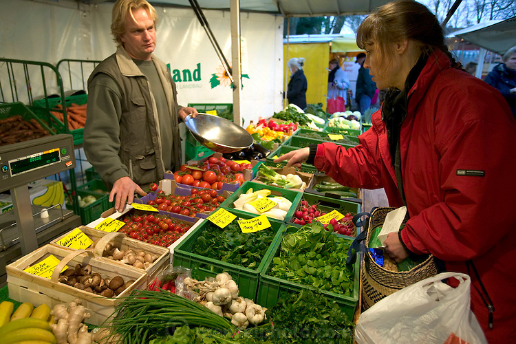 """At the outdoor Friday market in their tidy community of Bargteheide, Germany, Susanne Melander buys organic (""""bio"""") vegetables from a greengrocer. (Supporting image from the project Hungry Planet: What the World Eats.)"""
