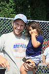 Actor Mark Feuerstein of USA's Royal Pains holds his daughter Addie as he played in the Artists vs. Writers 64th Annual Celebrity Softball Game on August 25, 2012 at Herrick Park, East Hampton, New York benefiting East End Hospice, East Hampton Day Care Learning Center, Phoenix Houses of Long Island and The Retreat.  (Photo by Sue Coflin/Max Photos)