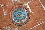 Downtown Historic Lancaster. Water valve cover with brick and snow dusting.