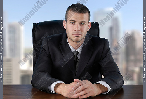 Businessman sitting at the desk in the office with a city view behind his back