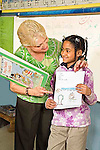 Blonde female teacher smiles and points to drawing and spelling list held by African American female second grade elementary smiling student in classroom