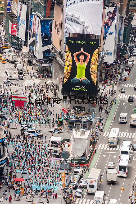 "Over 12,000 yoga practitioners pack Times Square in New York to practice yoga on the first day of summer, Wednesday, June 21, 2017. The 15th annual Solstice in Times Square, ""Mind Over Madness"",  stretches the yogis'  ability to block out the noise and the visual clutter that surround them in the Crossroads of the World. (© Richard B. Levine)"