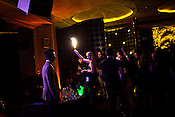 A woman lights up a flare while a bottle of champagne is popped in the background in The club LAP located in Hotel Samrat in New Delhi, India. Photograph: Sanjit Das/Panos