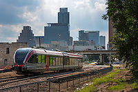 Capital MetroRail train speeds down the tracks to the Downtown Station located outside the Austin Convention Center on 4th St. between Neches & Trinity, inset I-35 upper deck during rush hour traffic and the Austin Skyline highrises.