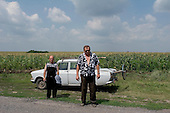 Uspenka, Ukraine.July 27, 2005 ..Near the a border crossing with Russia, Ivan Gorobtsov, 49, co-owns the field behind him. He and his partner also own two 20 year old combines.