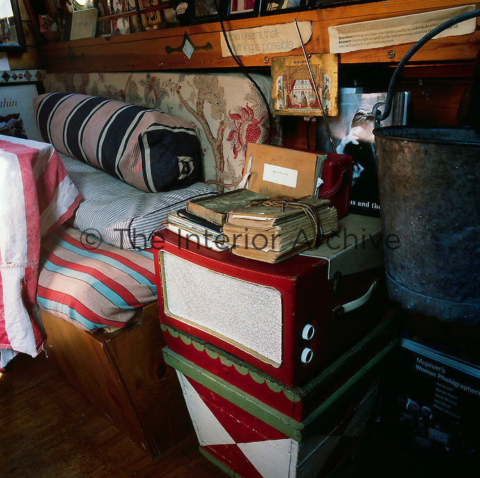 A vintage record player beside a bench seat in the dining area at the back of the houseboat