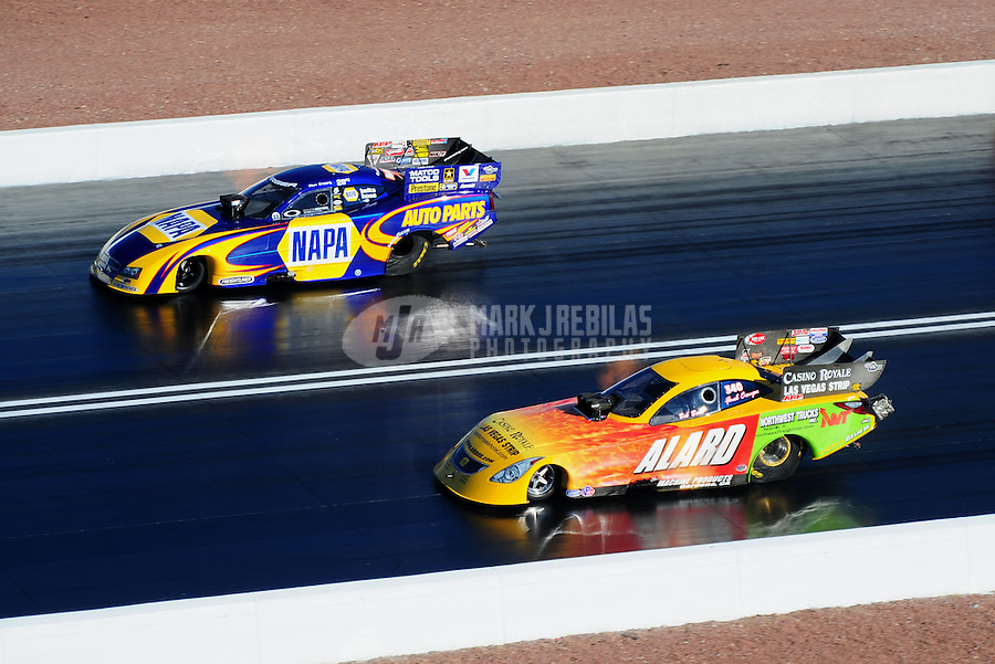 Apr. 1, 2011; Las Vegas, NV, USA: NHRA funny car driver Ron Capps (left) races alongside Bob Bode during qualifying for the Summitracing.com Nationals at The Strip in Las Vegas. Mandatory Credit: Mark J. Rebilas-