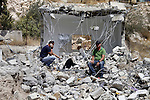 Shaker Ja'abis (L) sits on the rubble of his own home after demolishing it by bulldozer in Jabel Mukaber neighborhood southern Jerusalem on Sep 05, 2013. Ja'abis decided to demolish his own home to carry out an Israeli court order under the pretext of building without municipality permit. Many Palestinians end up demolishing their homes themselves to avoid the high cost of paying for Israeli government bulldozers, or being sent to prison for not being able to pay. Photo by Saeed Qaq