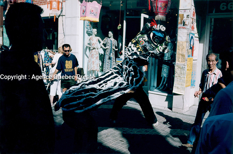 July 1995 file photo, Montreal, Quebec, Canada<br /> <br /> People look at the Dragon dance  in Montreal's Chinatown.<br />  <br /> <br /> Mandatory Credit: Photo by Pierre Roussel- Images Distribution. (©) Copyright by Pierre Roussel <br /> ON SPEC<br /> NOTE 8x10 print scanned AND,saved in Adobe 1998 RGB.