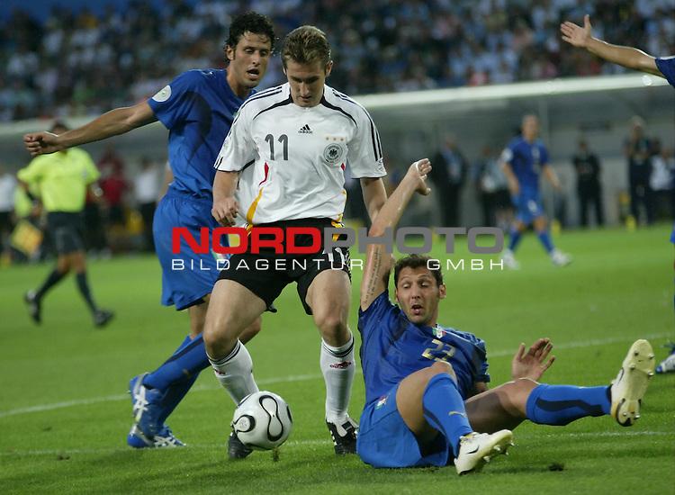 FIFA WM 2006 -  Semi Finals / Halbfinale<br /> Play    #61 (04-Juli) - Deutschland - Italien 0:2 n.V.<br /> <br /> Miroslav Klose (Mitte) von Deutschland im Zweikampf mit Fabio Grosso (links) und Marco Materazzi (am Boden) von Italien.<br /> <br /> Foto &copy; nordphoto