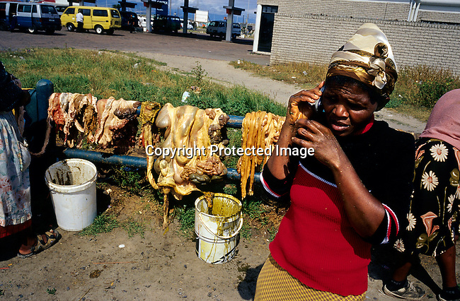 Zohdiwe Mewakbeni, age 42, talks on her mobile phone while selling cow intestines, popular for cooking traditional food, at a roadside market on October 7, 2003 in Khayelitsha, the biggest black township, about 20 miles outside Cape Town, South Africa. She has six children, all with different men. It's estimated that over one million people live here, most of them under appalling conditions in shacks with no running water or electricity. The township was founded in 1984. (Photo by: Per-Anders Pettersson).....