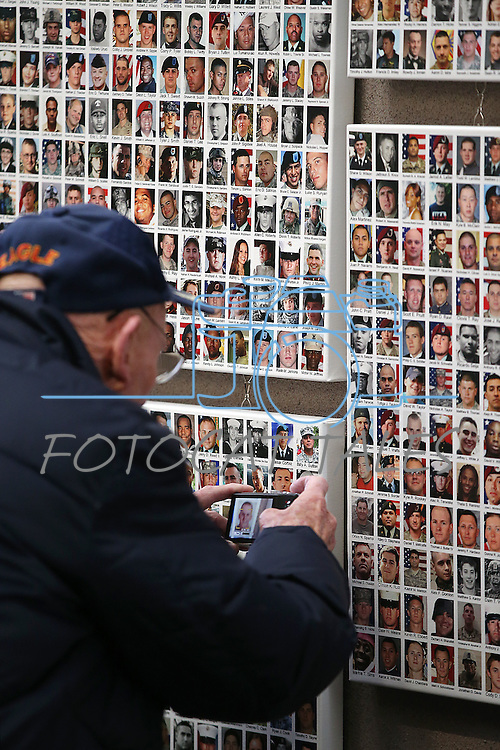 Harold Siegfried, of Carson City, takes a picture of his nephew on the Wall of the Dead at the opening ceremony of the Always Lost: A Meditation on War exhibit at the Legislative Building in Carson City, Nev., on Monday, April 6, 2015. His nephew Army Pvt. Theodore Rushing died Nov. 11, 2011 in Afghanistan. <br /> Photo by Cathleen Allison/Nevada Photo Source